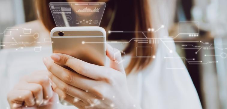 Mulher em abiente iluminado segurando seu smartphone em sua frente enquanto gráficos de dados fazem referência ao uso da LGPD e segurança da informação nas empresas