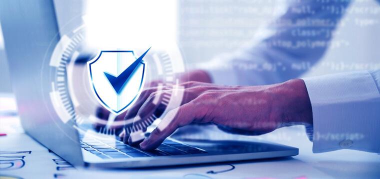 Homem digitando em um laptop na frente de um escritório. Alusão à lgpd